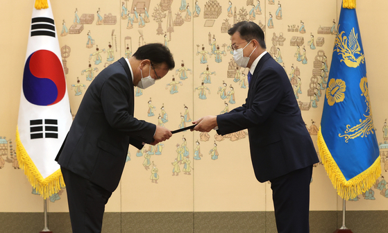 President Moon Jae-in, right, hands an appointment letter to Prime Minister Kim Boo-kyum at a ceremony at the Blue House on Friday.  [YONHAP]