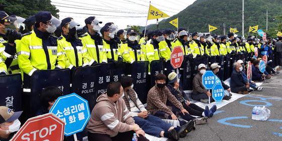 Police stand behind residents of Seongju County in North Gyeongsang on Tuesday as the residents attempt to block a road when the military deliver construction materials and daily necessaries to the Terminal High Altitude Area Defense (Thaad) base of the United States Forces Korea. [NEWS1]