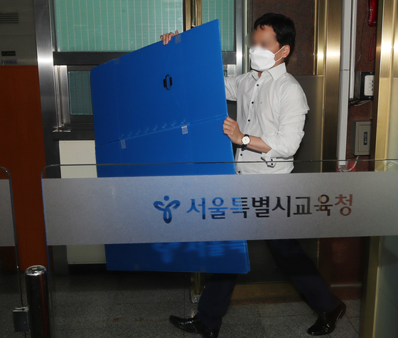 An official of the Corruption Investigation Office for High-ranking Officials enters the Seoul Metropolitan Office of Education on Tuesday to raid the office of Seoul's superintendent for education, Cho Hee-yeon, who has been accused of allegedly abusing his power to hire back sacked teachers. [YONHAP]