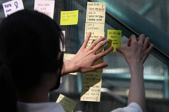 A woman attaches sticky notes with hand-written condolences on May 17 last year at Exit 10 of Gangnam Station, southern Seoul, marking four years since the murder of a 23-year-old woman by a stranger in a bathroom near the station in 2016. [NEWS1]