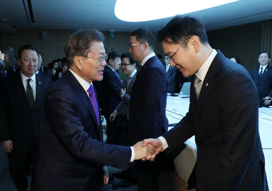 In this file photo, President Moon Jae-in, left, shakes hands with Samsung Electronics Vice Chairman Lee Jae-yong during a meeting with business leaders to discuss the country's response to the Covid-19 pandemic on Feb. 13, 2020. [Joint Press Corps]