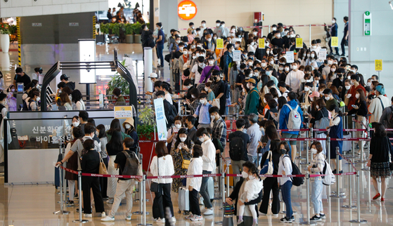 Travelers wait in long lines to board domestic flights at the departure terminal of Gimpo International Airport in Gangseo District, western Seoul, on Wednesday — Buddha's Birthday and also a national holiday. [NEWS1]