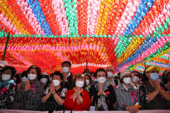 People pray at a service celebrating the 2,565th birthday of Buddha at Jogye Temple in Jongno District, central Seoul, on Wednesday. [OH JONG-TAEK]