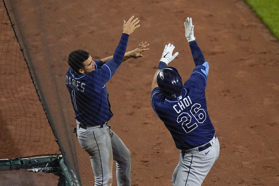 Tampa Bay Rays designated hitter Choi Ji-man, right, is greeted by Willy Adames near the dugout after hitting a two-run home run off Baltimore Orioles relief pitcher Shawn Armstrong during the eighth inning of a game on Tuesday in Baltimore. [AP/YONHAP]