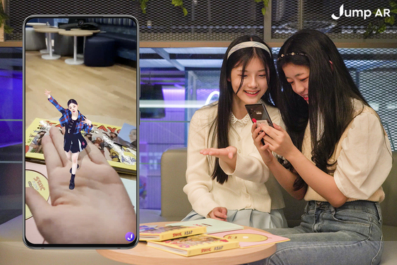 Models try out the ″digital human content″ AR service available on the Jump AR app created by SK Telecom, featuring girl group STAYC. The content has been created as a part of the telecom company's ″K-pop Metaverse Project.″ [SK TELECOM]