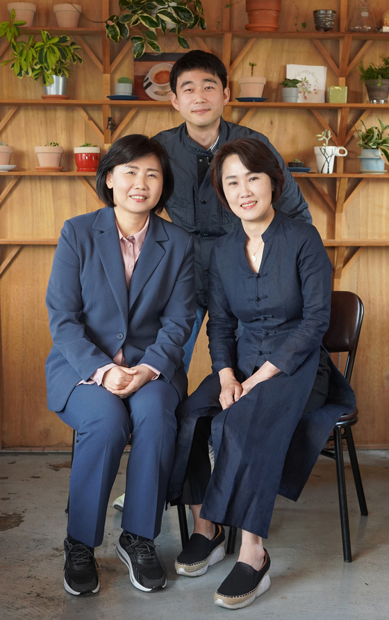 Director Kim Jung-in, center, and two of the mothers from the film ″A Long Way to School″ Lee Eun-ja, left, and Kim Nam-yeon, pose for photos after an interview with the Korea JoongAng Daily. [JEON TAE-GYU]