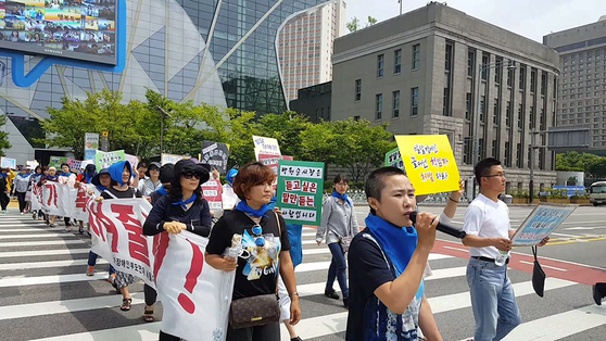 A still image from the film ″A Long Way to School″ shows families of people with disabilities rallying outside City Hall in central Seoul on April 2, 2016,is protest of the government's lowered budget for welfare for people with disabilities. [JINJIN PICTURES]