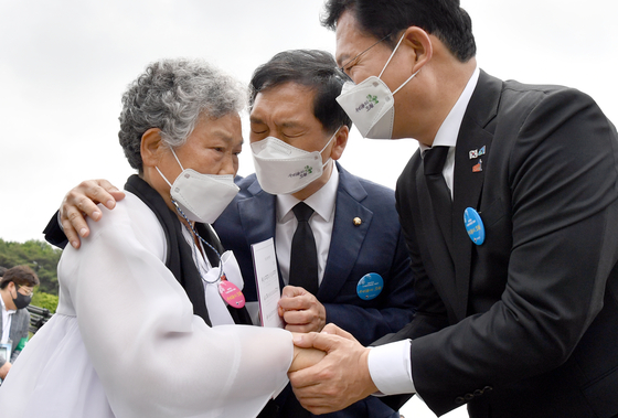 From right, ruling Democratic Party Chairman Song Young-gil and opposition People Power Party's acting Chairman Kim Gi-hyeon comfort a relative of a victim of the May 18 Gwangju Democratization Movement of 1980 at the May 18th National Cemetery in Gwangju on Tuesday. [YONHAP]
