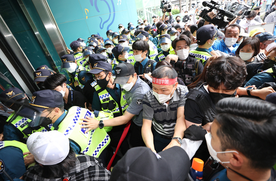 Owners of entertainment establishments, such as hostess bars and noraebang (singing rooms), clash with police on Thursday while attempting to storm into Seoul City Hall, demanding a ban, levied on their businesses because of fears of Covid-19 infection, be lifted. [YONHAP]