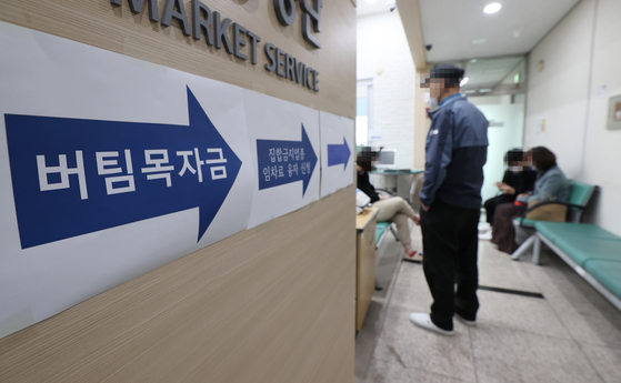 Applicants wait at a Small Enterprise and Market Service center in Jongno on April 26 to apply for government relief grants for small businesses. The government relief grants contributed to an increase in household income in the first quarter on year. [YONHAP]