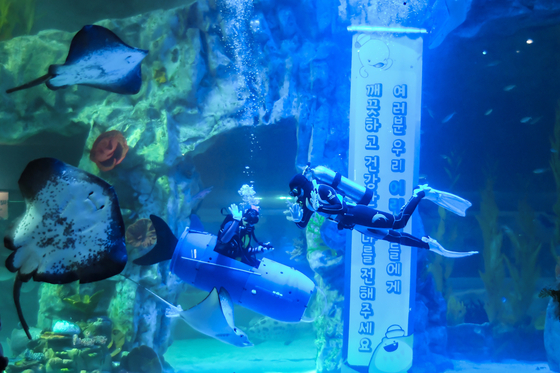 Lotte World Aquarium divers perform an act where they pick up trash underwater in order to raise awareness of environmental protection. Lotte said the performance will be held twice a day every weekend until the end of June. [LOTTE WORLD]