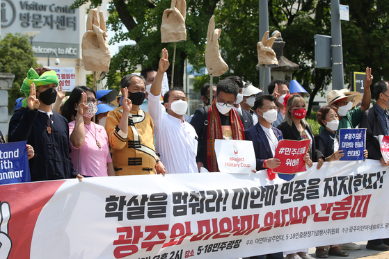 People make three-finger salutes at May 18 Democracy Square in Gwangju on Sunday during a rally in support of Myanmar protesters against a military coup. [YONHAP]