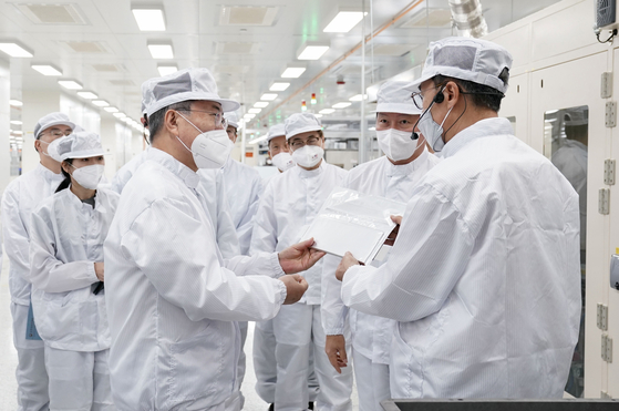 President Moon Jae-in, left, being briefed on EV batteries during his visit to SK Innovation's plant in Georgia, on Saturday. SK Group Chairman Chey Tae-won, second from right, attended the tour. [YONHAP]