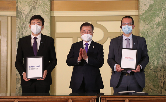 President Moon Jae-in, center, attends the signing ceremony for a supply agreement between Samsung Biologics CEO John Lee, left, and Moderna CEO Stephane Bancel in Washington, Saturday. [YONHAP]