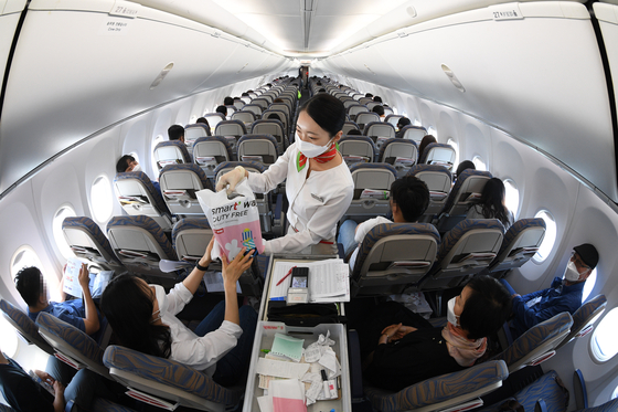 A T'way Air flight attendant handing duty-free purchases to a passenger on a flight to nowhere, that takes off and lands back where it started without an intermediate stop, between Daegu and Fukuoka, Japan. The budget airliner said Sunday that it has started its inflight duty-free shopping for customers getting on from the Daegu International Airport. [YONHAP]
