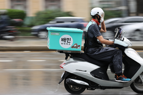 A Baedal Minjok food delivery rider in Seoul in 2020. The government started a program in which customers will get a 10,000-won refund for every four orders placed via food delivery apps to boost restaurant businesses hit by social distancing restrictions. [YONHAP]
