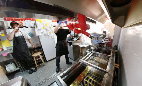 Robert Chicken's robot arm fries chickens in Gangnam, southern Seoul, while human staff receive orders and package food. [JEON TAE-GYU]