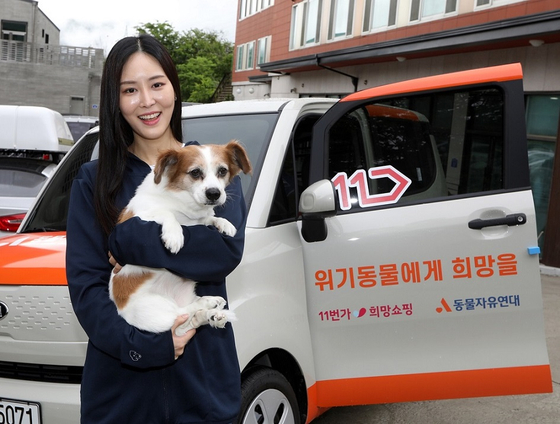 A model holds a dog in front of a Kia Ray, donated by 11st to the Korean Animal Welfare Association. 11st announced on Monday that the car was donated using the proceeds from a charity event sponsored by the e-commerce platform. The car will be used to transport animals from shelters to their families. [YONHAP]