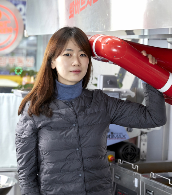 Robo Arete CEO Kang Ji-young poses beside the chicken-frying robot in Robert Chicken's second branch in Gangnam, southern Seoul. [JOONGANG PHOTO]