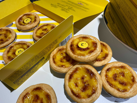 Image of Bang Si-hyuk, HYBE CEO, lies on top of egg tarts sold at HYBE Insight in central Seoul. [JIN MIN-JI]
