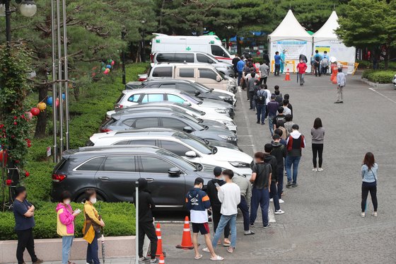 Citizens wait in line to get tested for Covid-19 at a temporary screening center in Daegu on Sunday. Infections tied to adult entertainment facilities are quickly increasing in the city, with 179 cases so far. [NEWS1]