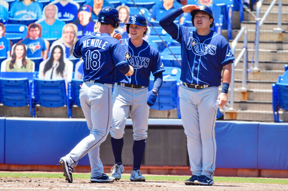Choi Ji-man, right, pretends to search the outfield as Joey Wendle and Taylor Walls of the Tampa Bay Rays celebrate after scoring in the first inning against the Toronto Blue Jays at Tropicana Field in St Petersburg, Florida on Monday. [AFP/YONHAP]