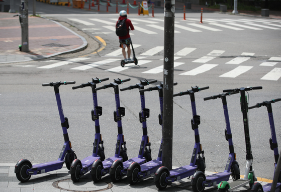 E-scooters parked around Hongik University in western Seoul on Tuesday. The once-popular ride has lost many users since tough restrictions, requiring a drivers license and helmet and banning more than one person from riding on the same scooter, were implemented from May 13.  [YONHAP]