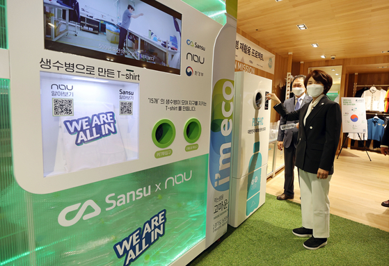 Environment Minister Han Jeoung-ae puts a plastic bottle into a crusher machine in Blackyak's Yangjae branch in Seocho District, southern Seoul, on Wednesday. The plastic bottle and T-shirt exchange event shows how plastic bottles can be recycled. [YONHAP]