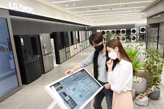 """Models look at a kiosk in the unmanned section of an LG Best Shop on Wednesday. According to LG Electronics, nine LG Best Shop branches will have a separate section in their venue that operates as a unmanned store after 8:30 p.m., making it the first local home appliance maker to operate an """"untact"""" store. [YONHAP]"""