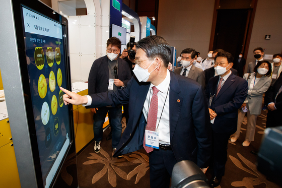 FSC Chairman Eun Sung-soo tests some of the fintech technologies exhibited at the Korea Fintech Week held at Conrad Hotel in Yeouido on Wednesday. [FINANCIAL SERVICES COMMISSION]