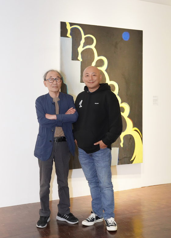 Artist Joo Jae-hwan, left, and webtoonist Joo Jae-Ho-min pose for photos after an interview with the Korea JoongAng Dailly in front of Joo Jae-hwan's painting ″Spring Rain Descending a Staircase″ (1980) at the ″Homin and Jaehwan″ exhibition held at the Seoul Museum of Art. [JEON TAE-GYU]