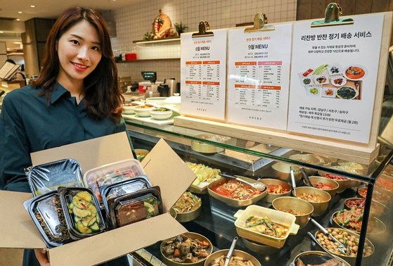A model shows Hyundai Department Store's subscription box. The subscription service delivers various side dishes and soups to customers every week. [HYUNDAI DEPARTMENT STORE]