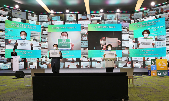 Korean Foreign Minister Chung Eui-young, left, and Environment Minister Han Jeoung-ae hold up messages on climate change, joined by hundreds of participants from around the world, at the opening ceremony of the Green Future Week at the Dongdaemun Design Plaza in central Seoul Monday, ahead of the P4G Seoul Summit. [PARK SANG-MOON]