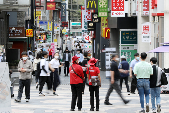 The government announced Wednesday that people who have had their first vaccine shot will be allowed to take off their masks outdoors starting in July. In addition, it announced the lifting of restrictions on gatherings for vaccinated people. In the photo, people are walking in Myeongdong in central Seoul with their masks on Wednesday. [NEWS1]