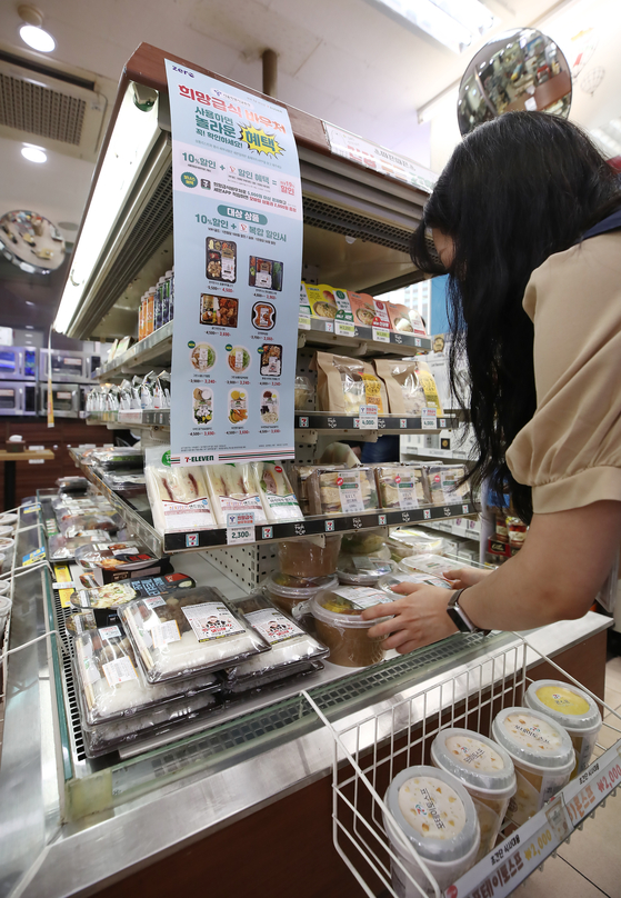 An employee arranges meals at a 7-Eleven store in Jung District, central Seoul, on Thursday. Convenience stores such as 7-Eleven, GS25 and Emart24 have released a series of meals that can be bought with student food vouchers. The vouchers, a replacement for school lunches that temporarily stopped during the pandemic, can only be used to purchase products that are nutritionally balanced with fewer than 990 kilocalories, 1,067 milligrams of sodium and more than 11.7 grams of protein. [YONHAP]