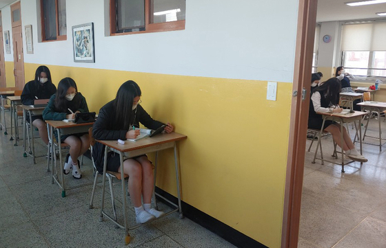 Students of a high school in Cheongju, North Chungcheong, have been divided, for some to take class in-person in the classroom, while others have been located to sit in hallways, to take the class being live-streamed on tablet PCs and other electronic devices, to ensure proper social distancing. [YONHAP]