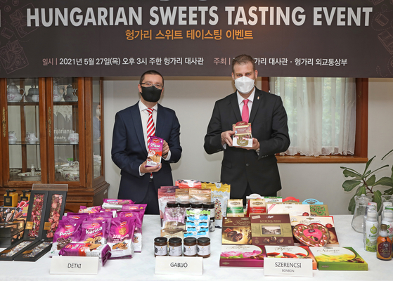 Mozes Csoma, ambassador of Hungary to Korea, right, poses for a photo with a box of chocolates during a Hungarian Sweets Tasting Event held at the Hungarian Embassy in Yongsan District, central Seoul, on Thursday. Products from a total of six Hungarian confectionery companies including chocoMe, Detki and Szerencsi Bonbon were introduced for tasting during the event as part of efforts to help Hungarian companies that wish to become export partners with the Korean market. [PARK SANG-MOON]