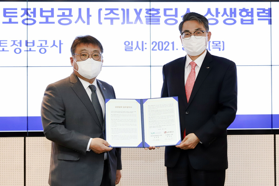 From left, LX Holdings CEO Song Chi-ho and LX CEO Kim Jung-ryul sign a memorandum of understanding at LX's Seoul office in Gangnam, southern Seoul, Thursday. [LX HOLDINGS]