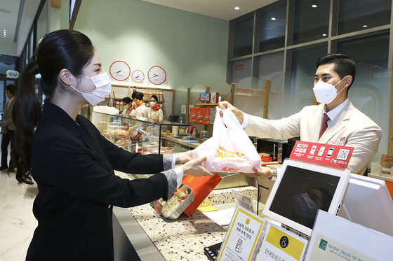 A Jeju Air flight attendant delivers an inflight meal package to a customer at its temporary offline restaurant in Hongdae, western Seoul. [JEJU AIR]