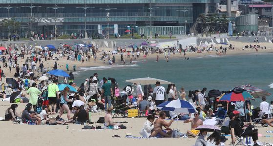 Tourists and locals cool off at Haeundae Beach in Busan on Sunday. As summer is coming, local governments announced plans to fully open beaches in July. Until then, some of the most popular beaches, like Haeundae Beach, will limit the number of people when they partially open this Tuesday. [SONG BONG-GEUN]