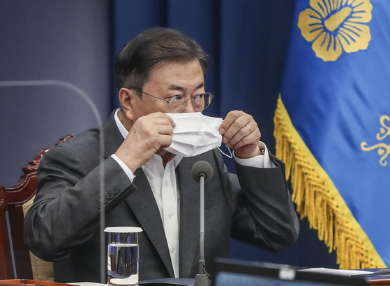 President Moon Jae-in puts on a mask after finishing his speech at a meeting with his aides at the Blue House on May 17 [KIM SEONG-RYONG]