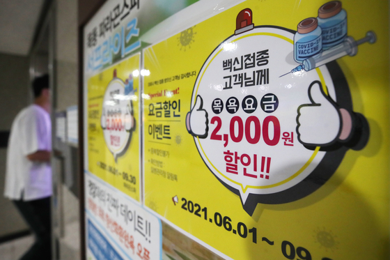 A sign at a sauna in Seoul offering a 2,000 won ($1.80) discount to visitors who have received the coronavirus vaccine on Sunday. Many companies, including restaurants and saunas, are coming up with various discount promotions targeting customers who are ready to go outdoors after getting vaccinated. [YONHAP]