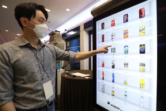 An employee demonstrates a digital vending machine during an invention event organized by the Korean Intellectual Property Office and the Korea Invention Promotion Association at the 63 Convention Center in Seoul on Monday. [NEWS1]
