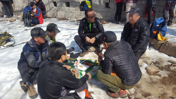 A group of hikers are drinking makeolli near the Daedongmun Gate at Mt. Bukhansan in March 2018. [KOREA NATIONAL PARK]