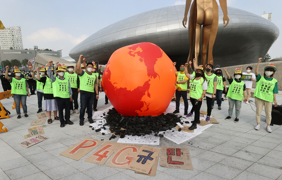 Civic group members stage a performance to raise awareness of carbon emissions by displaying a burning earth structure in front of Dongdaemun Design Plaza in central Seoul on Monday, where the P4G Summit was held. [YONHAP]