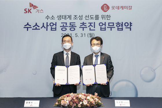 Lotte Chemical CEO Kim Gyo-hyun, left, and SK Gas CEO Yoon Byung-suk sign an agreement to cooperate in hydrogen businesses, at SK Gas's office in Pangyo, Gyeonggi, on Monday. [LOTTE CHEMICAL]