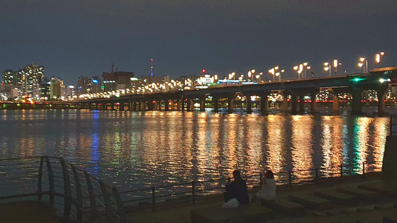 People drink right beside the water in Yeouido Han River Park in western Seoul, on May 21 around 11 p.m. [HALEY YANG]