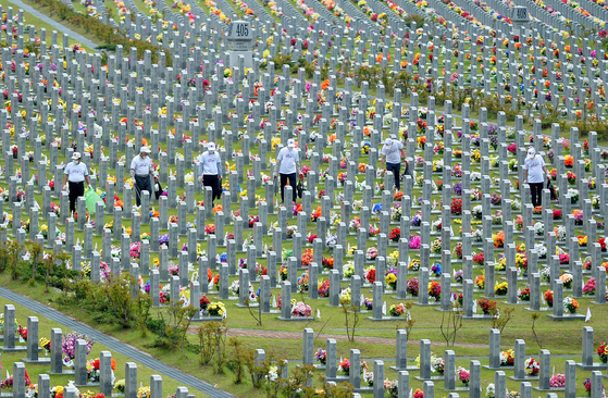 Several Vietnam War veterans clean graves of fallen soldiers at the National Cemetery in Daejeon on Monday, six days ahead of Memorial Day on June 6. [KIM SEONG-TAE]