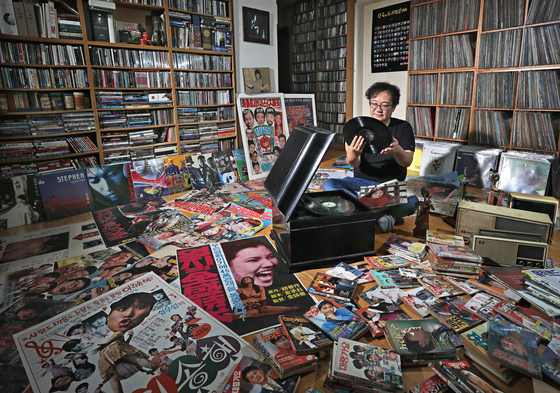Pop music critic Choi Kyu-sung examines his collection of LPs, CDs, cassette tapes, songbooks, posters and more at the K-pop Database & Research Institute in Jori-eup in Paju, Gyeonggi. [PARK SANG-MOON]