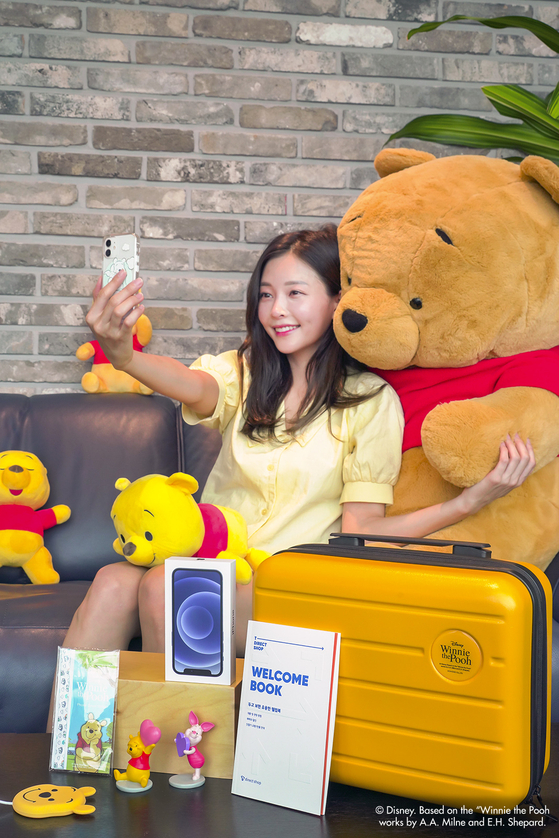 A model poses to promote SK Telecom's T Direct Shop Disney Special Edition. The promotional deal includes a white iPhone 12 mini with a Winnie the Pooh-themed charger, phone case and stickers. Customers who purchase the special edition can receive a discount coupon of their choice from either Baedal Minjok, 11st, One Store or CU every month, for up to one year. [YONHAP]
